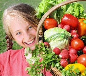 Smiling girl with basket of healthy vegetables