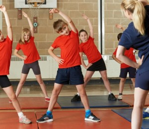 Active Students Exercise Class In School Gym